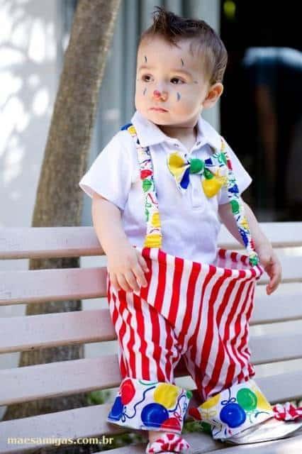 Criança vestida de palhaço, com rosto pintado.