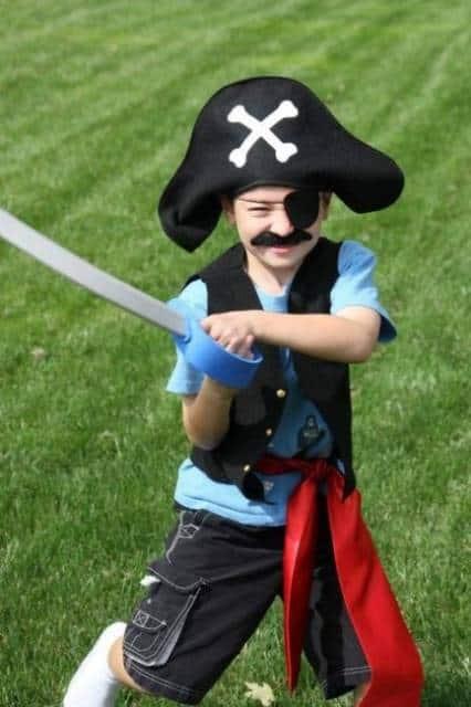 Menino com espada e chapéu de pirata.