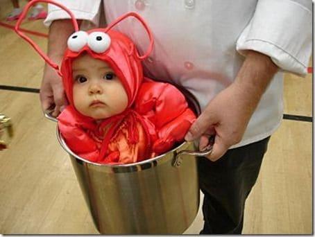 Bebê vestido de lagosta dentro de balde.