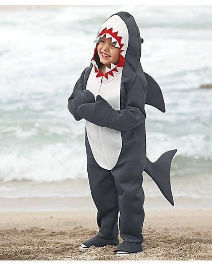 Menino dentro de fantasia de tubarão.