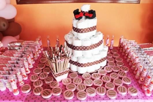 Decoração de chá de fraldas simples para menina em tons de rosa com bolo de fraldas