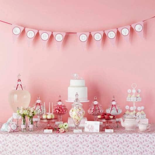 Decoração de chá de fraldas simples para menina em tons de rosa com flores naturais