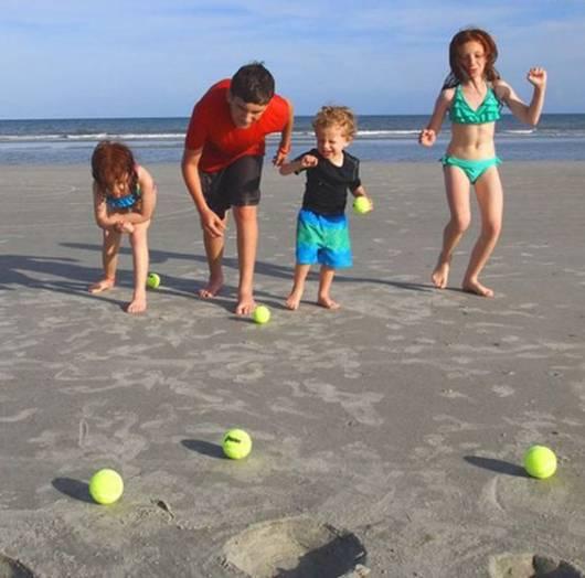 Crianças brincando com bolinhas de tênis na praia.