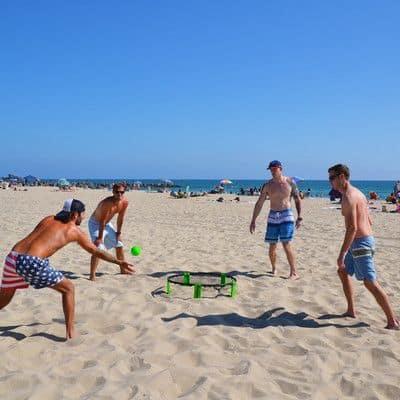Quatro homens brincando com uma bola e cama elástica.