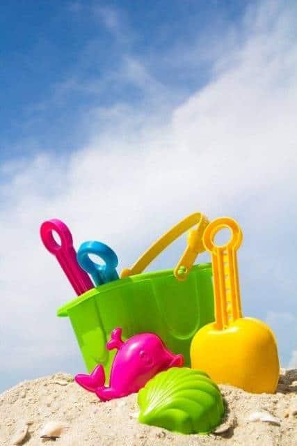 Balde verde com outros brinquedos de praia.