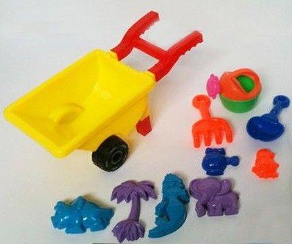 Carrinho de mão pequeno com formas, rastelo e outros brinquedos de praia.