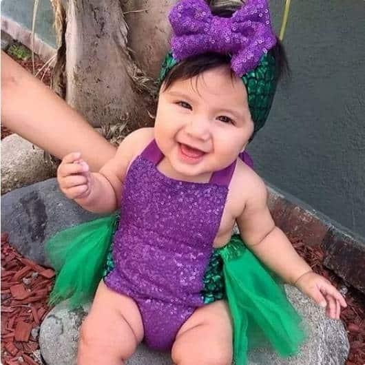 Bebê usando fantasia Ariel, com body roxo e saia verde.