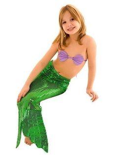 Menina vestindo saia verde de lantejoulas e top com formato de conchas.