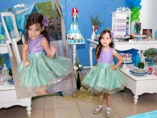 Criança usando vestido com cores de fantasia ariel.