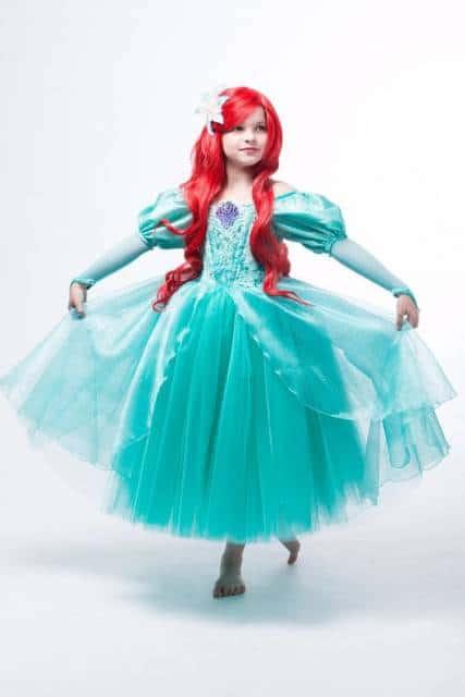 Criança com vestido verde, com detalhes roxos e peruca vermelha,