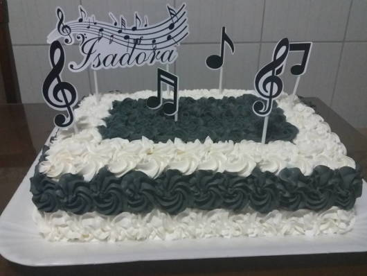 Bolo simples decorado com chantilly e toppers musicais