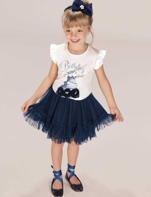 Menina com look com blusa branca e saia azul marinho