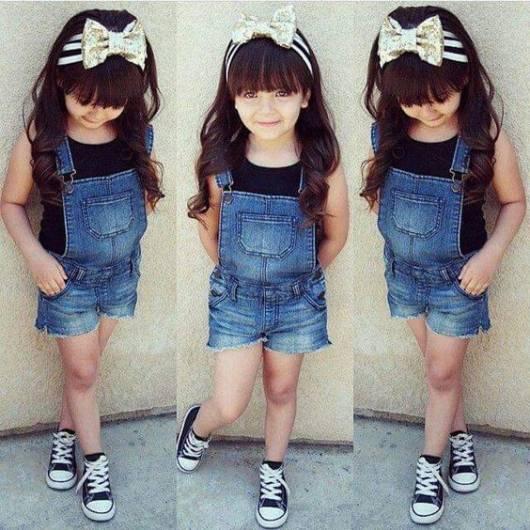 Menina com macacão jeans curto e camiseta preta.