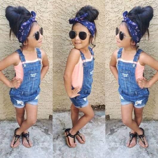 Criança com macacão jeans curto. óculos de sol e bandana.