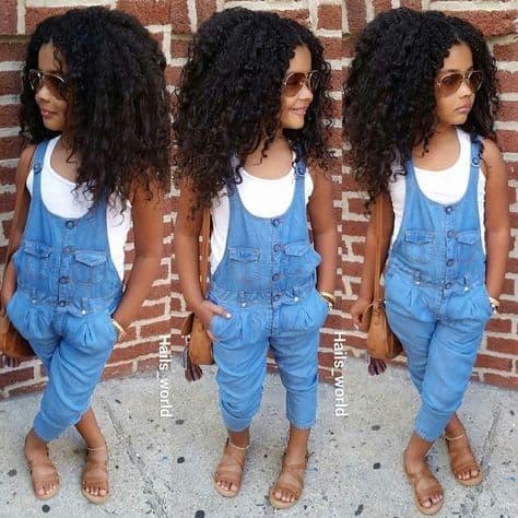 Menina com camiseta branca e macacão jeans comprido.