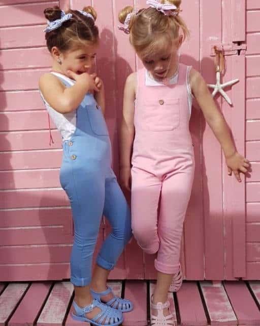 Foto de duas meninas usando macacão, um com a cor rosa e o outro, azul.