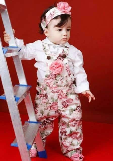 Criança usando macacão florido, com faixa na cabeça combinando.
