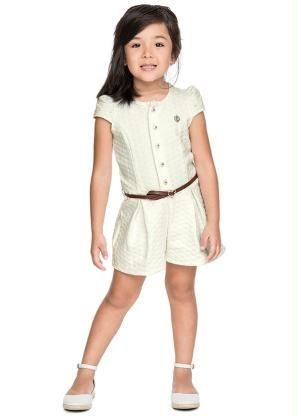 Menina usando macacão branco curto.