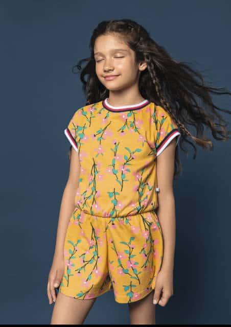 Menina usando macacão amarelo florido.