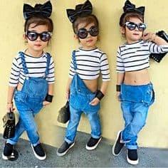 Criança usando macacão jeans comprido, cropped listrado e óculos de sol.