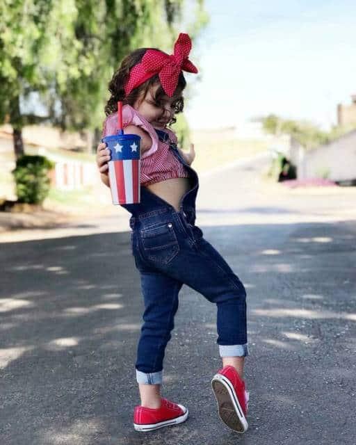 Menina com macacão jeans e laço vermelho na cabeça.