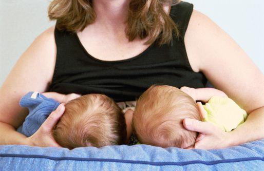 Mulher amamentando duas crianças.