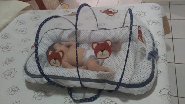 Bebê no ninho com mosquiteiro