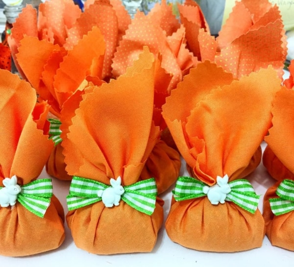 Saquinhos alaranjados de TNT com doces para a Páscoa