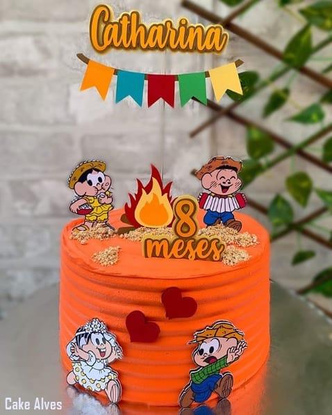 bolo coberto com chantilly laranja e tema de festa junina